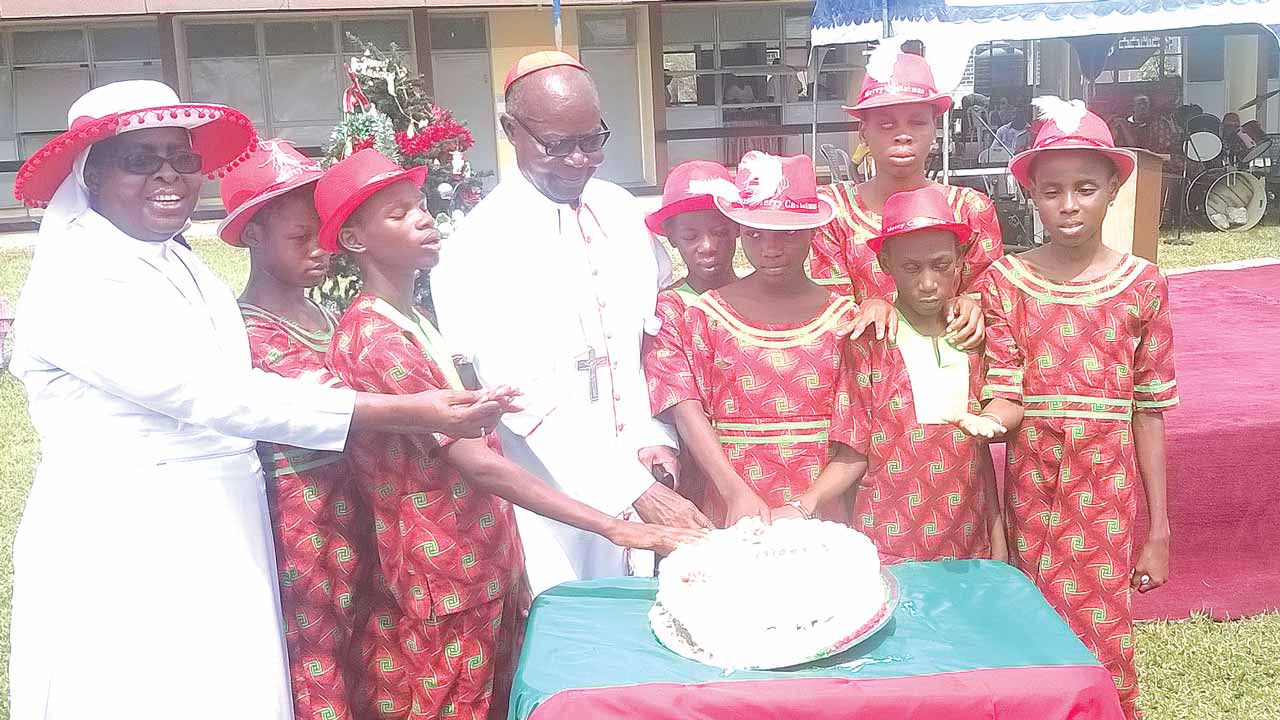 Archbishop Emeritus of Lagos, Anthony Cardinal Okogie (centre) flanked by the Principal of Pacelli School for the Blind and Partially Sighted Children in Surulere, Lagos, Sister Jane Onyeneri (left) and the children, during the Carol and Drama Service of the school                                                                                                                                                                                                                                       PHOTO: VICTOR GBONEGUN