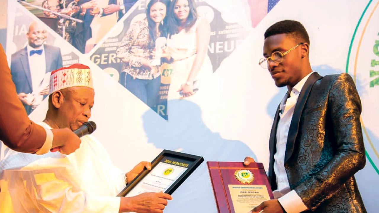 Oreoluwa Osoba receiving his role model award from the governor of Kano State, Abdullahi Ganduje