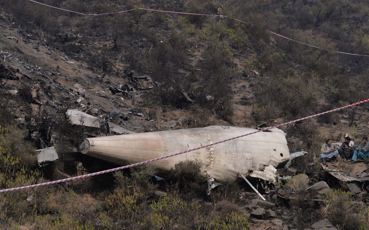 Pakistani sit beside the wreckage of the crashed PIA passenger plane Flight PK661 near the village of Saddha Batolni in the Abbottabad district of Khyber Pakhtunkhwa province on December 8, 2016. A Pakistani aircraft carrying 47 people issued a Mayday call before losing radar contact and crashing into a mountain, killing everyone on board, authorities said, as they began collecting DNA to identify victims. / AFP PHOTO / AAMIR QURESHI