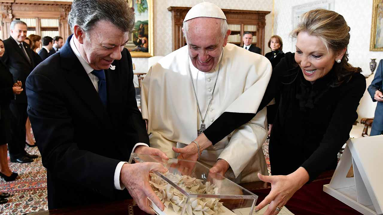 "Pope Francis (R) receives the ""Bun of the peace"" from Colombian president Juan Manuel Santos (L) and his wife prior to a meeting, on December 16, 2016 at the Vatican. VINCENZO PINTO / POOL / AFP"