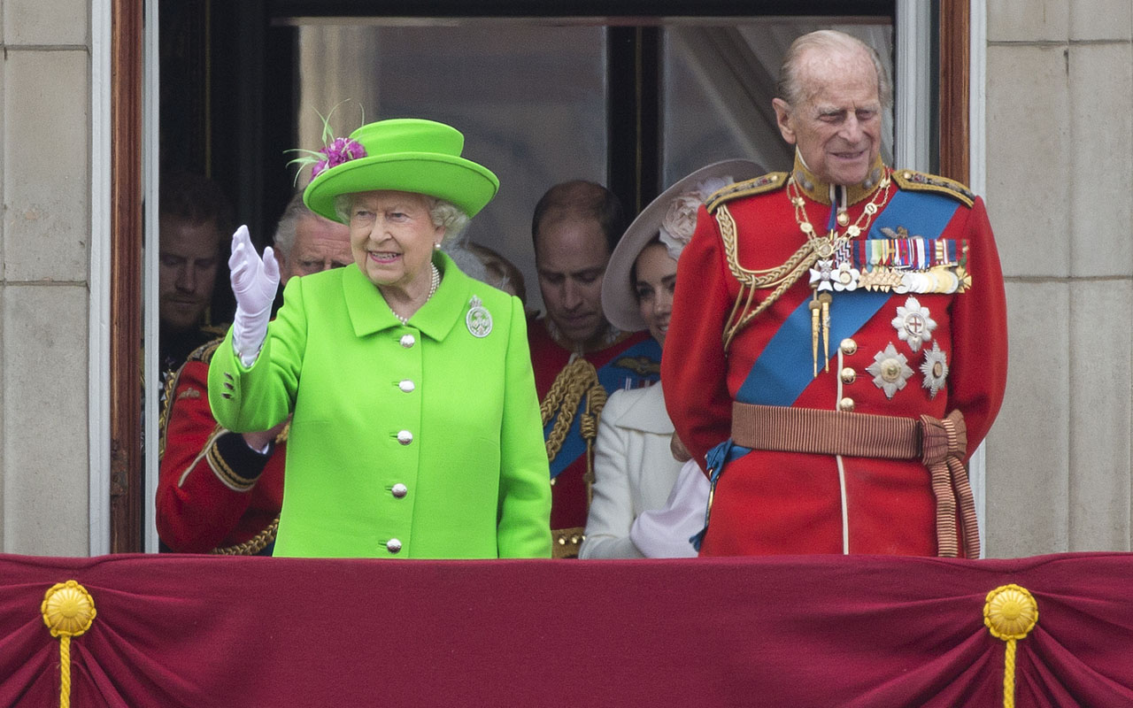 "(FILES) This file photo taken on June 11, 2016 shows (L-R) Britain's Queen Elizabeth II and Prince Philip, Duke of Edinburgh waving from the balcony of Buckingham Palace to watch a fly-past of aircrafts by the Royal Air Force, in London on June 11, 2016 during the annual Queen's 90th birthday celebration. Queen Elizabeth II has cancelled her departure on December 21, 2016 for a Christmas trip to her country estate because she and her husband have ""heavy colds"", a Buckingham Palace spokesman said. The 90-year-old monarch and her 95-year-old husband Prince Philip had been expected to travel from London as part of a yearly tradition. / AFP PHOTO / JUSTIN TALLIS"