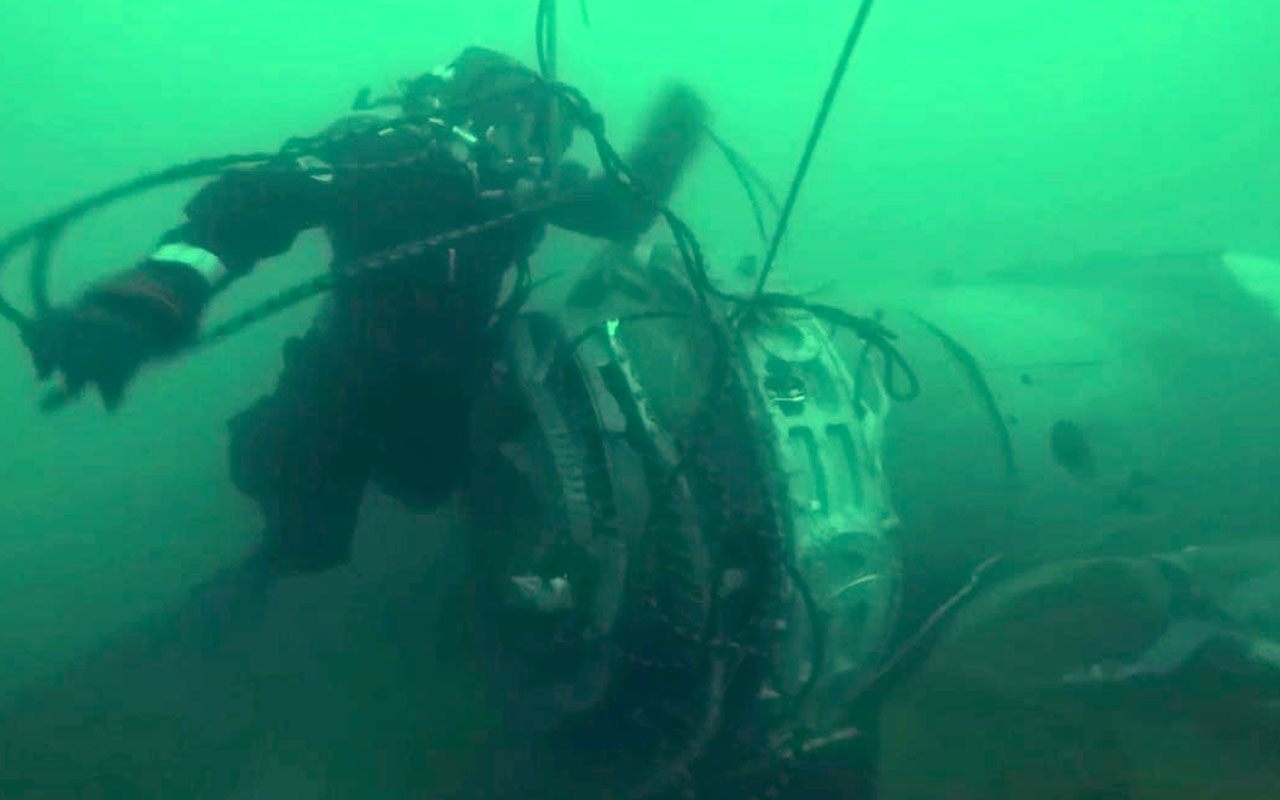 This handout video grab released by Russian Emergency Ministry on December 28, 2016, shows shows a diver looking at a piece of the crashed military plane carrying 92 people, including dozens of members of the Red Army Choir, during searches in the underwater area outside Sochi, in the Black Sea. Russian rescuers working round the clock have found the main black box from the Syria-bound military plane that crashed into the Black Sea with 92 people on board, authorities said on December 27, 2016. The discovery of the black box comes as searchers scramble to recover bodies and remaining debris from the aircraft in an operation involving divers, deepwater machines, helicopters and drones. The Tu-154 jet, whose passengers included more than 60 members of the internationally renowned Red Army Choir, was heading to Russia's military airbase in Syria on December 25 when it went down off the coast of Sochi shortly after take-off from a refuelling stop at the airport. / AFP PHOTO / RUSSIAN EMERGENCY MINISTRY / HO /