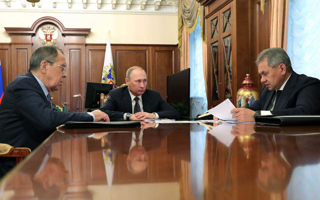 Russian President Vladimir Putin speaks with Defence Minister Sergei Shoigu (R) and Foreign Minister Sergei Lavrov (L) during their meeting at the Kremlin in Moscow / AFP PHOTO / Sputnik / Michael Klimentyev