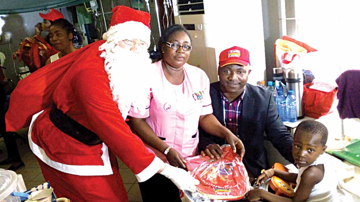 Santa Claus presenting a gift toBaby Joshua Fatuyi. Others are  Mrs.  Ajibola and Ashiwaju at LASUTH