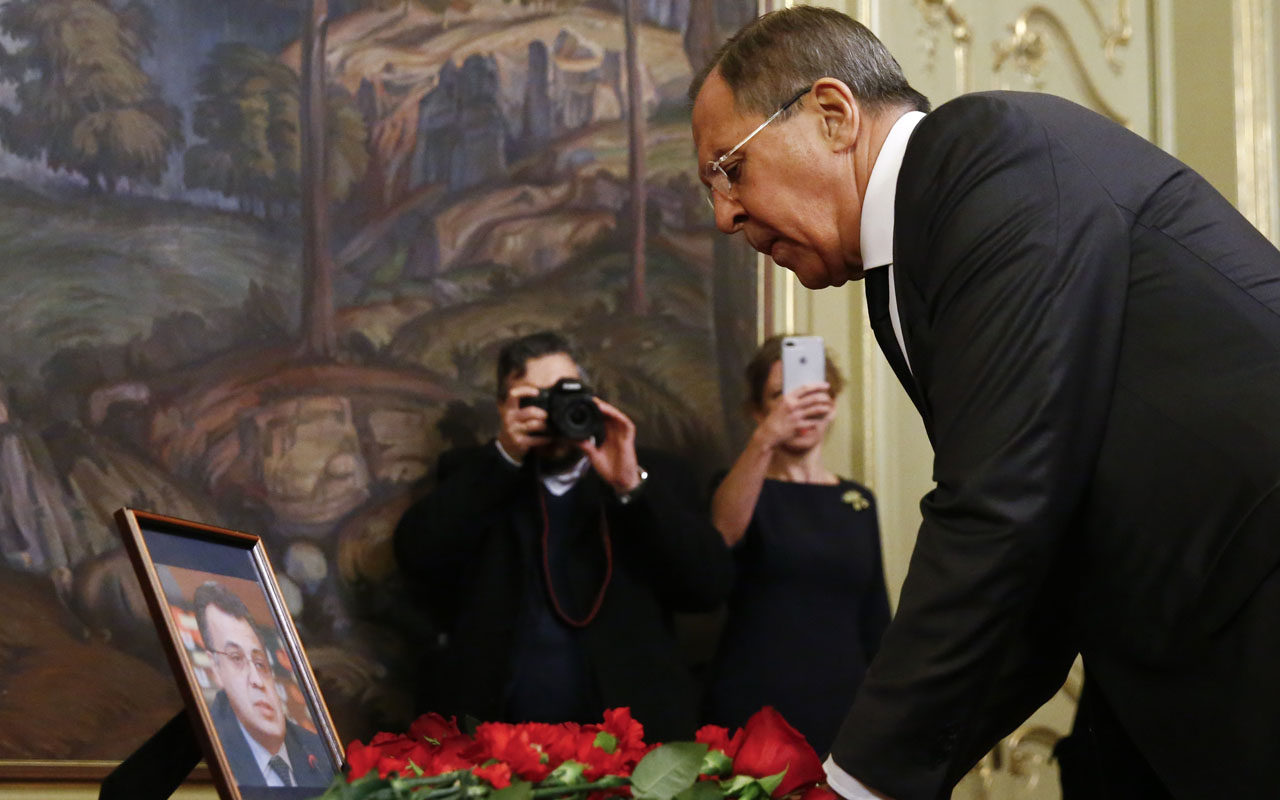 "Russian Foreign Minister Sergei Lavrov lays flowers in front of a photo of Russian ambassador to Turkey, who was killed in Ankara, before talks with his Iranian counterpart in Moscow on December 20, 2016. A Turkish policeman crying ""Aleppo"" and ""Allahu Akbar"" shot dead Russia's ambassador to Turkey in Ankara on December 19, prompting a vow from President Vladimir Putin to step up the fight against ""terrorism."" Andrei Karlov died of his wounds after the shooting in an Ankara exhibition centre, which came on the eve of a key meeting in Moscow between the Russian, Turkish and Iranian foreign ministers on the Syria conflict. / AFP PHOTO / MAXIM SHEMETOV"