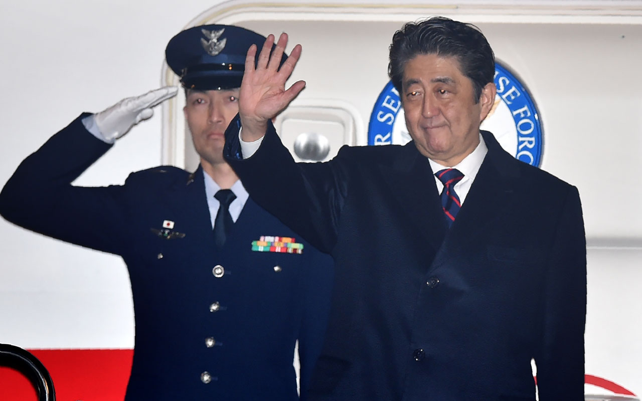 Japan's Prime Minister Shinzo Abe (R) waves before departure for Hawaii at Tokyo's Haneda airport on December 26, 2016. Abe departed on December 26 for Hawaii where he will visit Pearl Harbor with US President Barack Obama as the two countries highlight decades of post-World War II reconciliation. / AFP PHOTO / KAZUHIRO NOGI