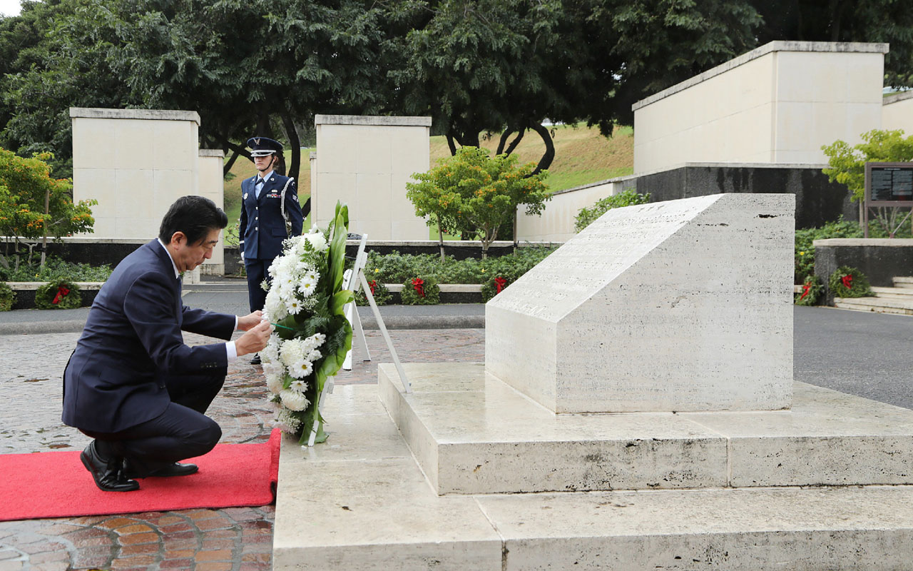 Japanese Prime Minister Shinzo Abe places a wreath at the National Memorial Cemetery of the Pacific at the Punchbowl in Honolulu, Hawaii on December 26, 2016. Japan's Prime Minister Shinzo Abe arrived in Hawaii on December 26 ahead of a symbolic meeting with President Barack Obama at the site of the Pearl Harbor attack. Abe's visit comes 75 years after Japan's December 1941 attack on the base of the US Pacific fleet, drawing the US into World War II. / AFP PHOTO / JAPAN POOL VIA JIJI PRESS / STR / Japan OUT