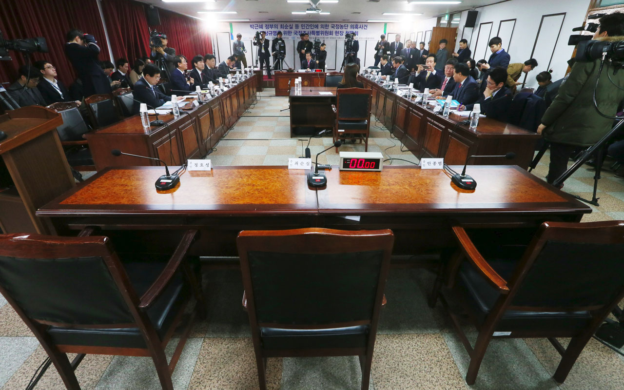 The empty seat (C) of Choi Soon-Sil, a long-time friend of South Korean President Park Geun-Hye, is seen during a parliamentary probe into a scandal as lawmakers set up a special hearing to question Choi at the detention centre where Choi is being held in Uiwang, south of Seoul, on December 26, 2016. South Korean lawmakers sought on December 26 to question the woman at the heart of a corruption scandal that triggered the impeachment of President Park Geun-Hye, as special prosecutors raided the home of a former top presidential aide. / AFP PHOTO / YONHAP / STR / South Korea OUT /