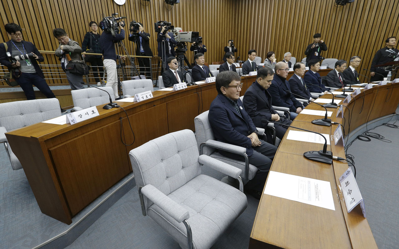 The empty seat (bottom R) of Choi Soon-sil, who is accused of colluding with South Korean President Park Geun-hye to control government affairs and extort companies, is seen during a hearing at the National Assembly in Seoul on December 7, 2016. A South Korean parliamentary probe into a corruption scandal engulfing President Park Geun-Hye sought December 7 to compel the woman in the eye of the storm to answer questions after she rejected a summons. / AFP PHOTO / POOL / Ahn Young-joon