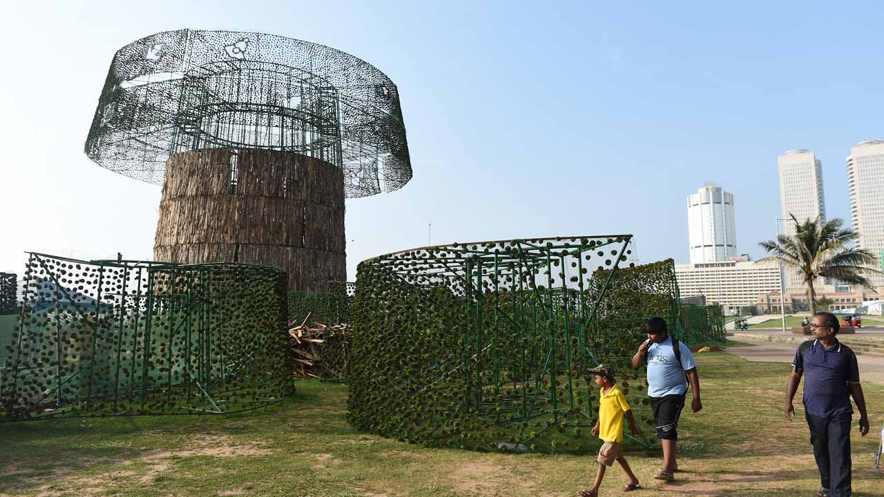 This file photograph taken on December 7, 2016, shows Sri Lankan pedestrians as they walk past a partially-constructed Christmas tree in Colombo. Sri Lanka surpassed the world record for the tallest artificial Christmas tree on December 24, 2016, despite building delays forcing organisers to prune the structure by almost half, an official said. Cricket legend Arjuna Ranatunga initiated plans to build the record-breaking tree in Sri Lanka's capital Colombo, but ran into opposition from the Catholic church which said the money would be better spent on charity. Ishara S. KODIKARA / AFP