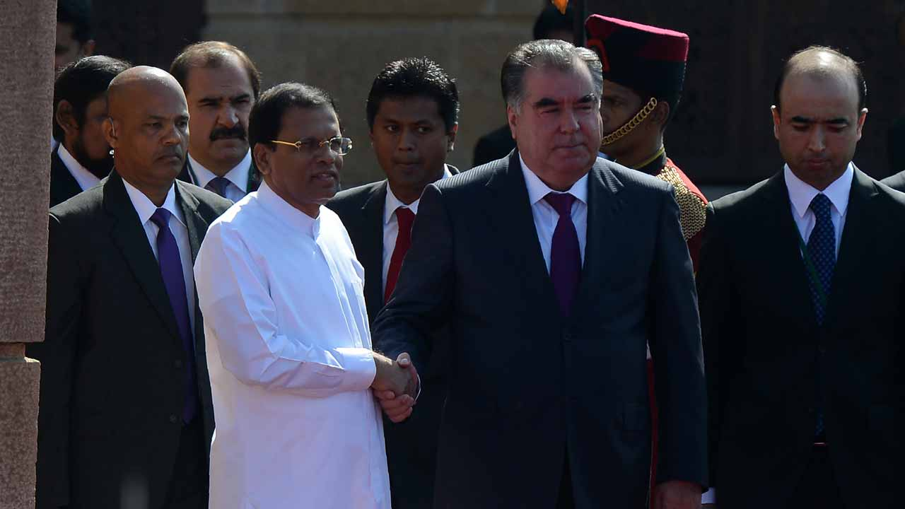 President of Tajikistan Emomali Rahmon (C) shakes hands with Sri Lankan President Maithripala Sirisena (2R) during a welcoming ceremony at the Presidential Secretariat in Colombo on December 13, 2016. Rahmon is on a three day official vist to Sri Lanka. LAKRUWAN WANNIARACHCHI / AFP