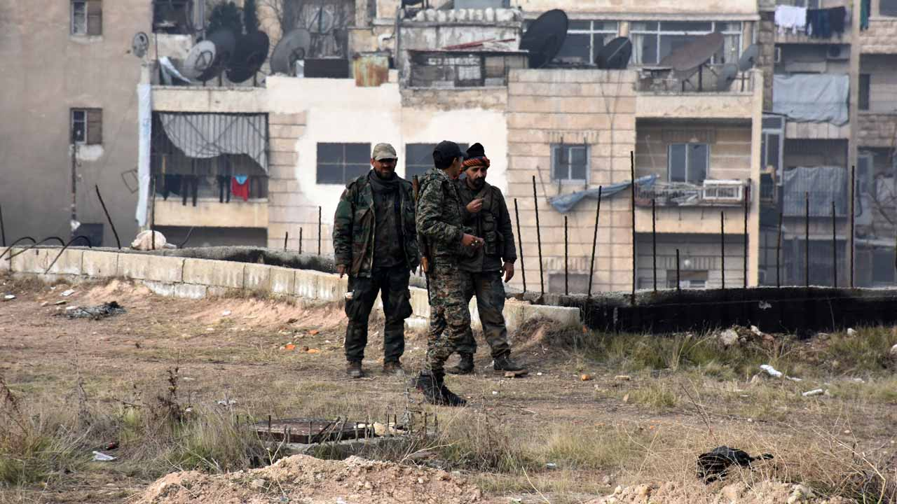 Syrian pro-government forces walk in west Aleppo's Ithaa district on December 11, 2016 after they retook the area from rebel fighters. Thousands of civilians poured out of rebel areas of Aleppo as Syria's army pushed to take the last remnants of opposition-held territory in the devastated city. George OURFALIAN / AFP