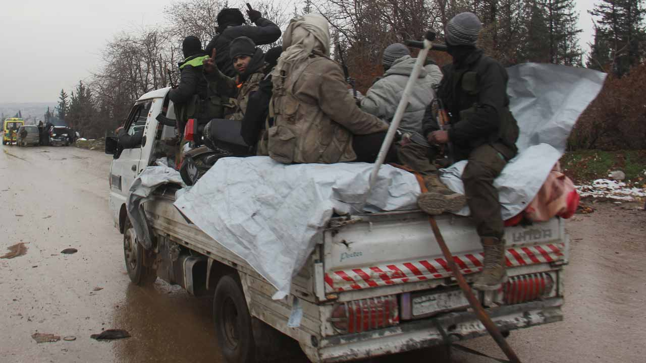 Syrian rebels being evacuated from Aleppo drive through a rebel-held territory near Rashidin, west of the embattled city, on December 22, 2016. Convoys carried opposition fighters out of the last rebel pocket of Aleppo in the final phase of an evacuation clearing the way for Syria's army to retake the city. As part of the Aleppo evacuation deal, it was agreed that some residents would be allowed to leave Fuaa and Kafraya, two Shiite-majority villages in northwestern Syria that are under siege by the Sunni Muslim rebels. Omar haj kadour / AFP