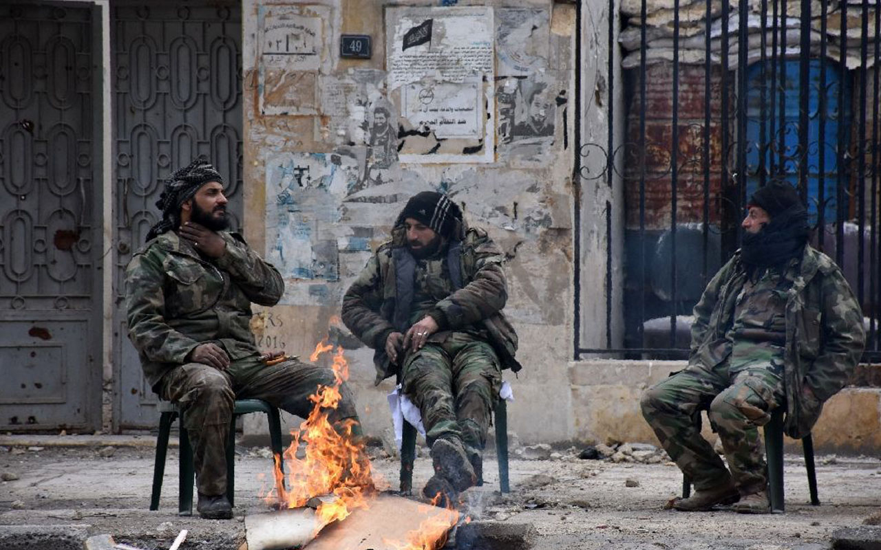 Syrians soldiers sit by a fire in the former rebel-held Ansari district of Aleppo, on December 23, 2016 (AFP Photo/George Ourfalian)