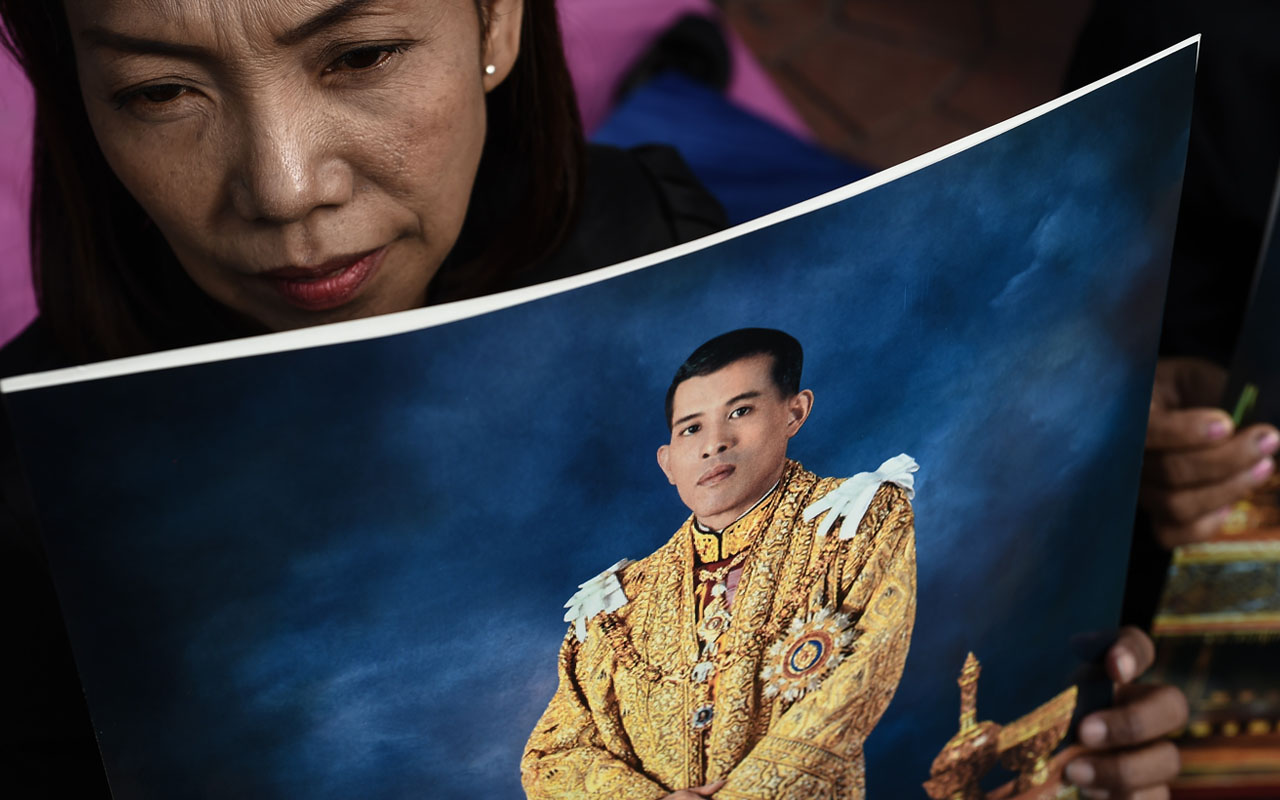 A woman holds an image of Thailand's new King Maha Vajiralongkorn outside the Grand Palace in Bangkok on December 2, 2016.  Crown Prince Maha Vajiralongkorn became the king of Thailand late on December 1, opening a new chapter for the powerful monarchy in a country still mourning the death of his father. / AFP PHOTO / Lillian SUWANRUMPHA
