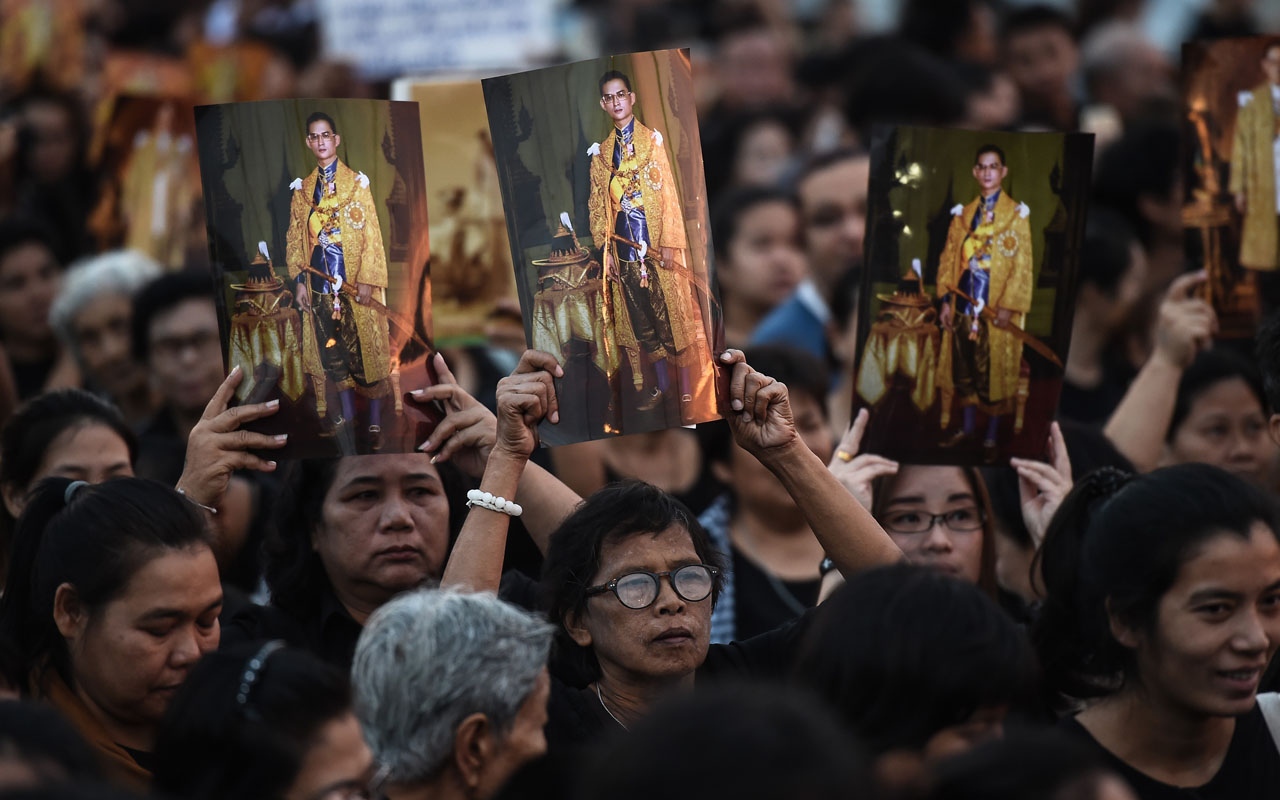 Mourners hold aloft pictures of the late Thai King Bhumibol Adulyadej as people gather to commemorate his birthday on top of Bhumibol Bridge in Bangkok on December 5, 2016. / AFP PHOTO / LILLIAN SUWANRUMPHA