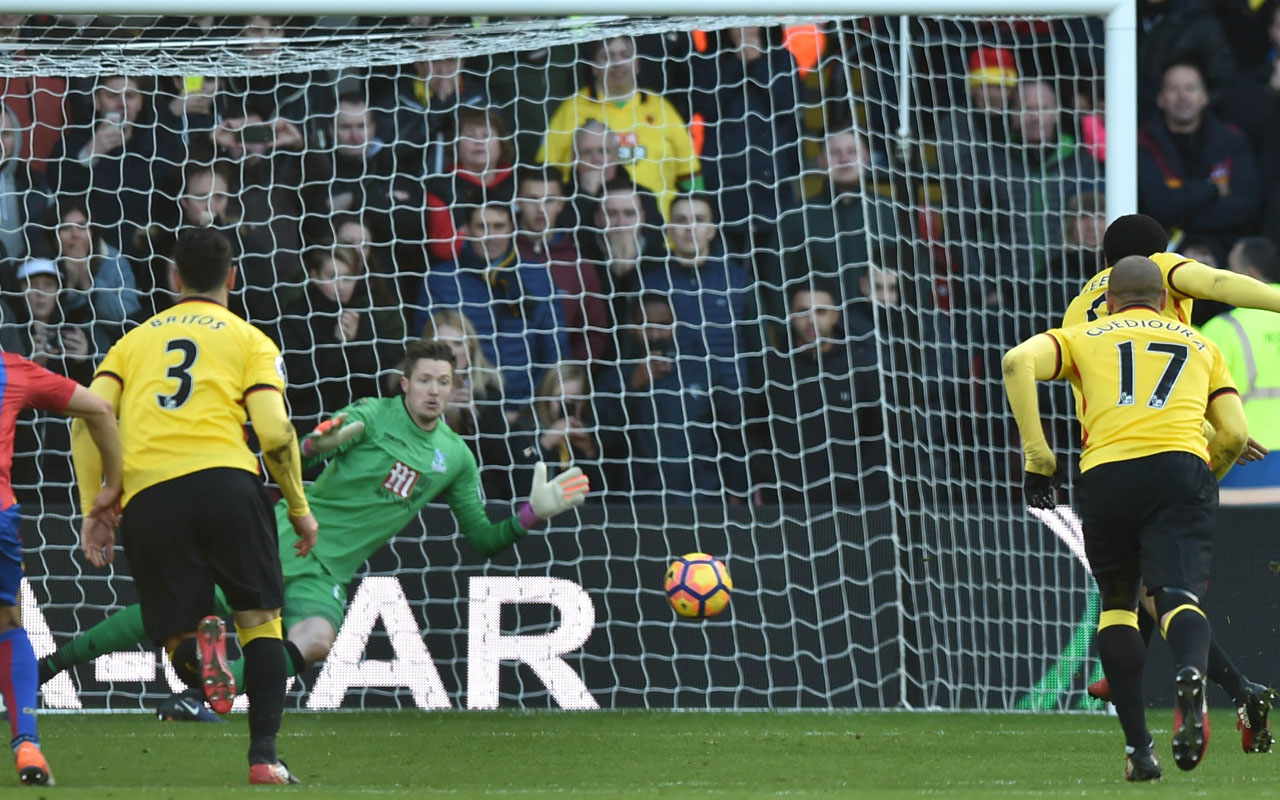 Watford's English striker Troy Deeney (R) scores their penalty past Crystal Palace's Welsh goalkeeper Wayne Hennessey (C) during the English Premier League football match between Watford and Crystal Palace at Vicarage Road Stadium in Watford, north of London on December 26, 2016. The game finished 1-1. / AFP PHOTO / OLLY GREENWOOD /
