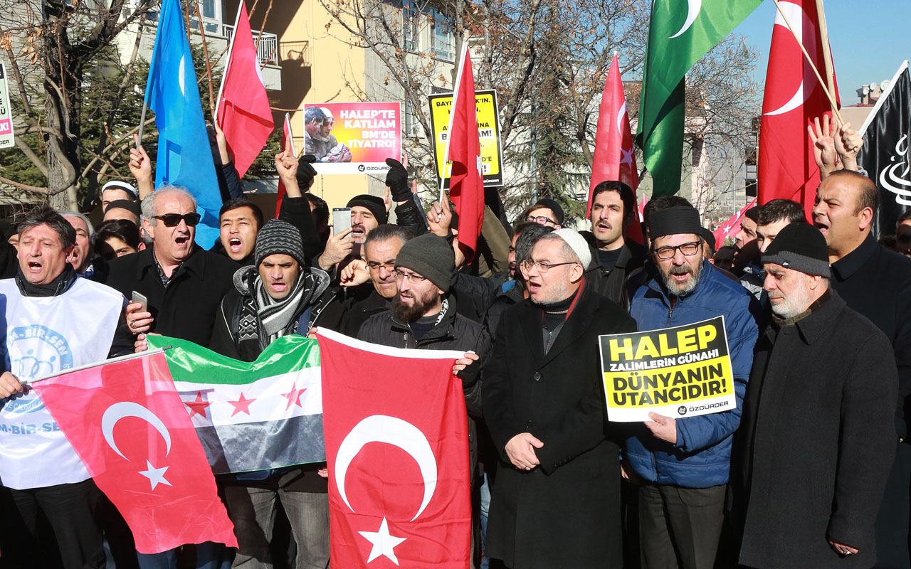 "Protesters hold a Syrian opposition flag, Turkish flags, and placards reading ""Massacre in Aleppo, theatre at the UN!"" and ""Aleppo is the world's shame!"" as they gather outside the Russian embassy in Ankara on December 15, 2016, during a demonstration against Russia's support of the Syrian regime. / AFP PHOTO / ADEM ALTAN"