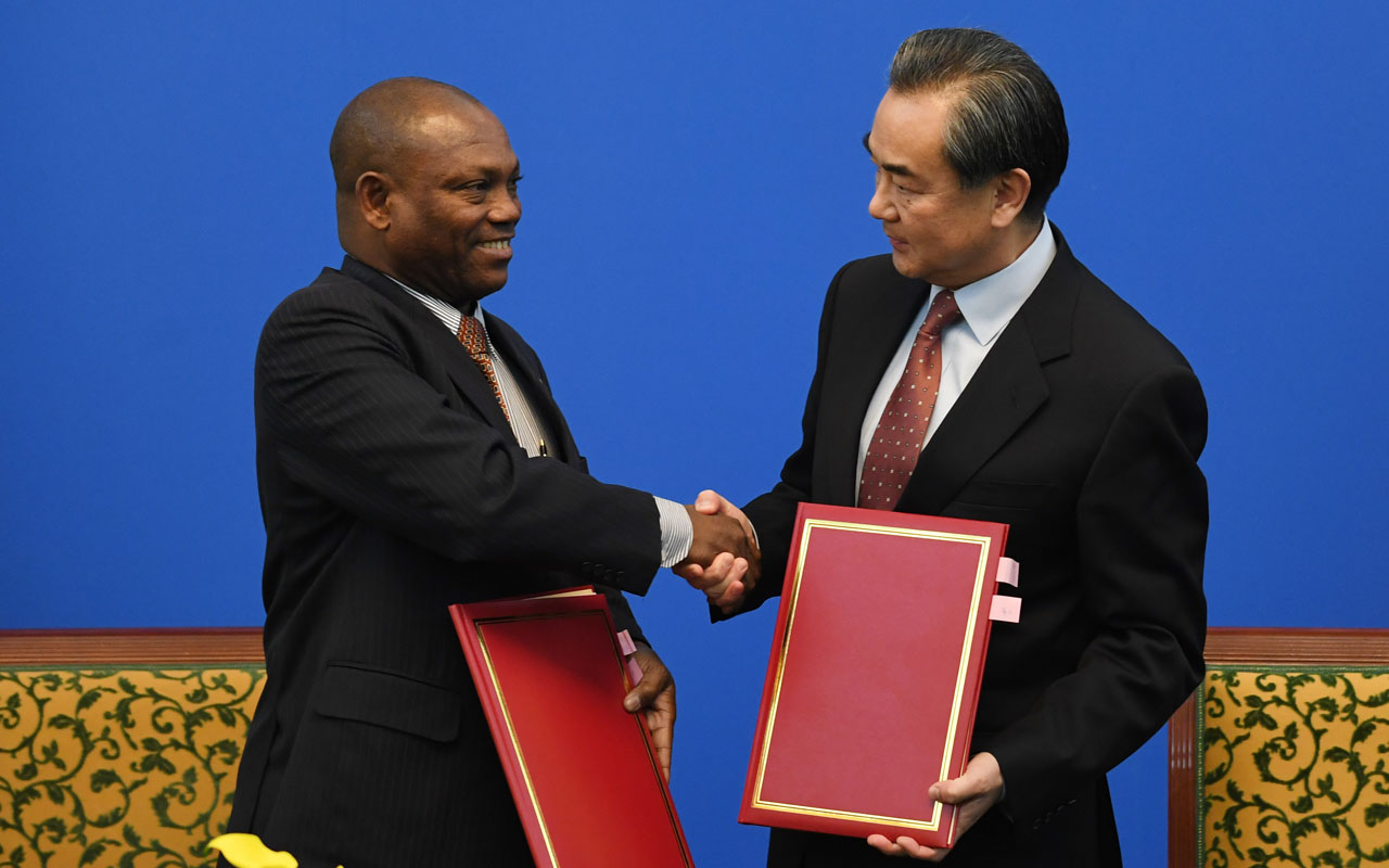 Chinese Foreign Minister Wang Yi (R) shakes hands with his Sao Tome counterpart Urbino Botelho after signing an agreement in Beijing on December 26, 2016. China and Sao Tome signed an agreement to restore diplomatic relations on December 26, 2016, just days after the small African nation announced it had cut ties with Taiwan. / AFP PHOTO / GREG BAKER /