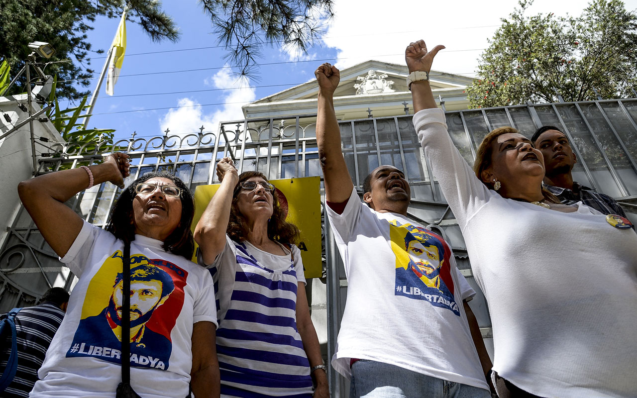 Opposition activists in Venezuela shout slogans demanding that the leftist government of Nicolas Maduro order the release of political prisoners, outside the Nunciature in Caracas, on December 6, 2016. / AFP PHOTO / FEDERICO PARRA