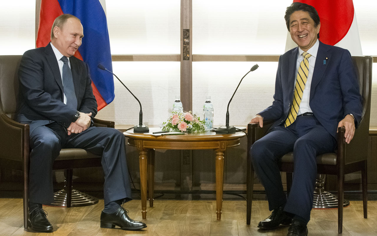 Japanese Prime Minister Shinzo Abe (R) and Russian President Vladimir Putin (L) smile at the start of their summit meeting in Nagato, Yamaguchi prefecture on December 15, 2016. Putin is on a two-day official visit to Japan. / AFP PHOTO / POOL / Alexander Zemlianichenko