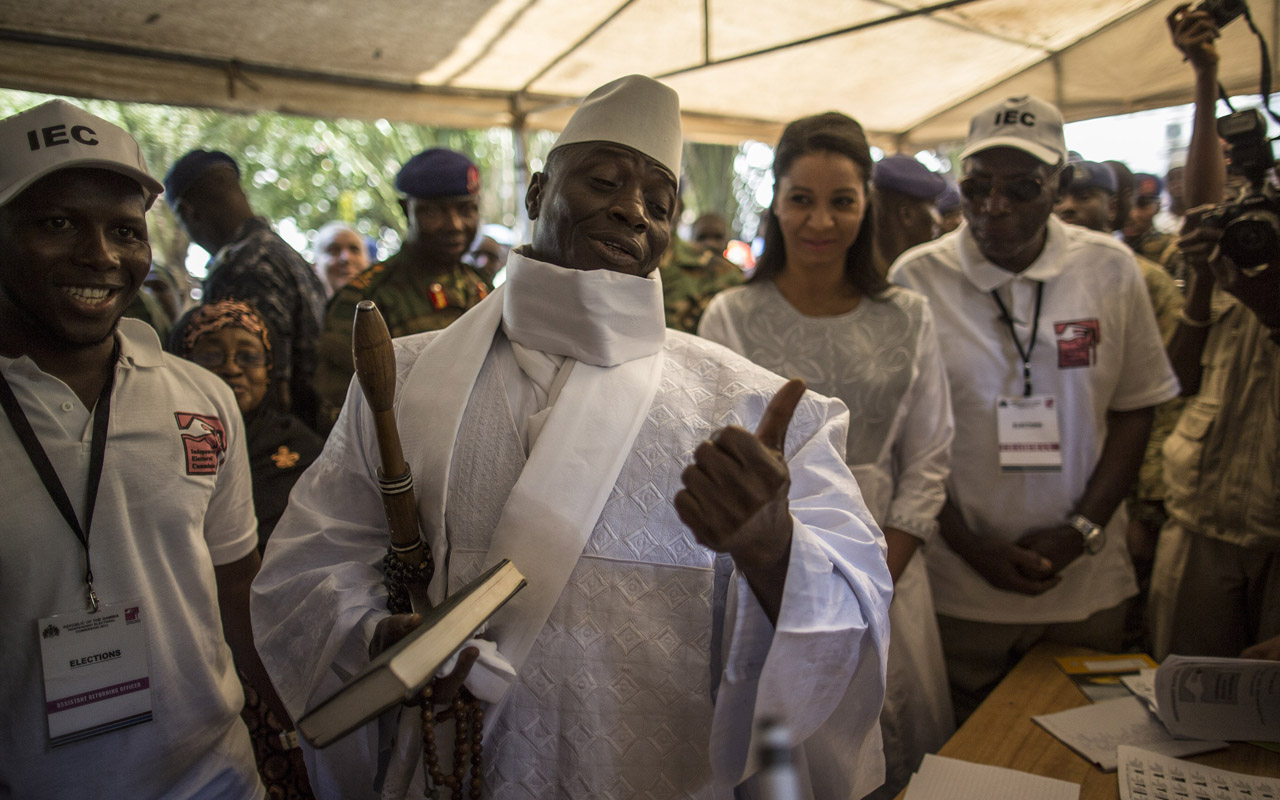 "Incumbent Gambian president Yahya Jammeh (C) gestures before casting his marble in a polling station in a presidential poll, in Banjul on December 01, 2016. The first of some 880,000 eligible voters headed to polling stations despite an internet blackout imposed overnight in a nation long accused by rights groups of suppressing freedom of expression. The Gambia's unique voting system, which sees citizens vote by dropping a marble into a coloured drum for their candidate, could not be rigged, he added, meaning ""there is no reason for anybody to protest."" / AFP PHOTO / MARCO LONGARI"