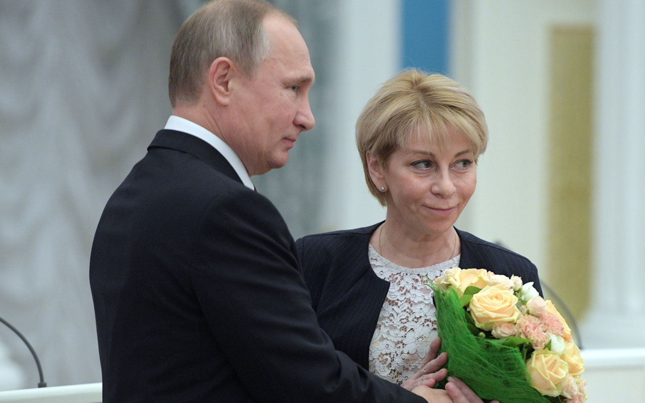A picture taken on December 8, 2016 shows Russian President Vladimir Putin (L) offering flowers to Yelizaveta Glinka (Doctor Liza), executive director of the Fair Aid International Public Organization, during a ceremony to give out national awards for outstanding achievements in human rights and charity activity. Charity activist Elizaveta Glinka or Dr. Liza was on board the Tu-154 travelling to Syria to celebrate the New Year with Russian troops. More than 60 members of the internationally-renowned Red Army Choir were on board a Russian military plane that crashed in the Black Sea on December 25, 2016, Russia's defence ministry said. / AFP PHOTO / SPUTNIK / Alexei Druzhinin