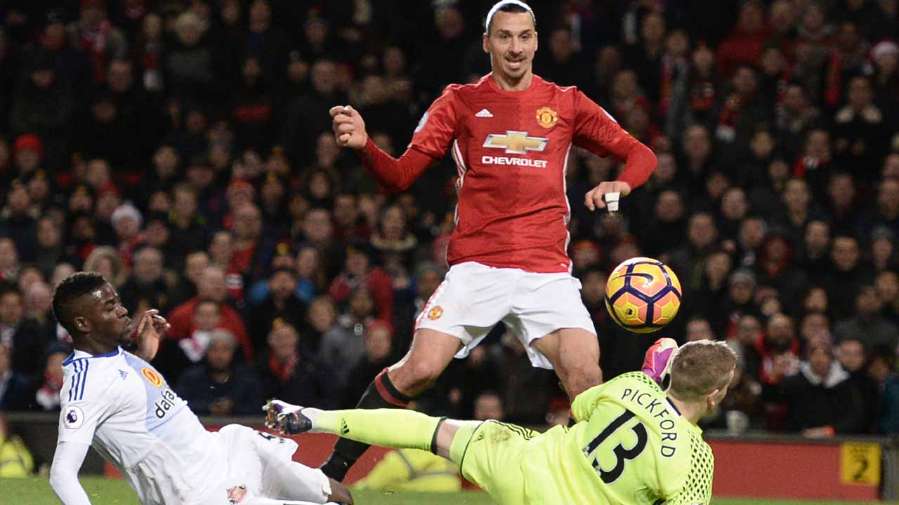 Manchester United's Swedish striker Zlatan Ibrahimovic (C) lifts the ball over Sunderland's English goalkeeper Jordan Pickford (R) to score their second goal during the English Premier League football match between Manchester United and Sunderland at Old Trafford in Manchester, north west England, on December 26, 2016. Oli SCARFF / AFP