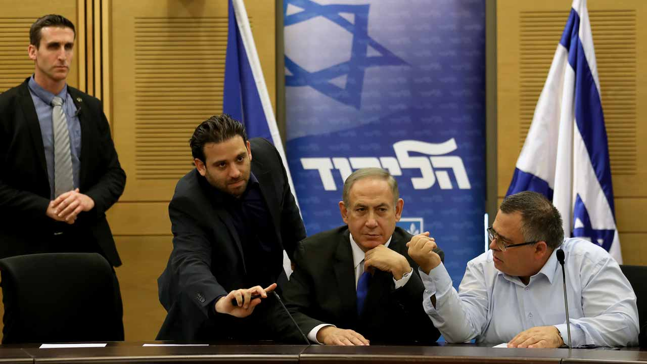 "Israeli Prime Minister Benjamin Netanyahu (C) looks on during a Likud faction meeting at the Knesset (Israel's Parliament) in Jerusalem on January 2, 2017. Netanyahu denied any wrongdoing ahead of his expected questioning by police in a graft probe, telling his political opponents to put any ""celebrations"" on hold. GALI TIBBON / AFP"