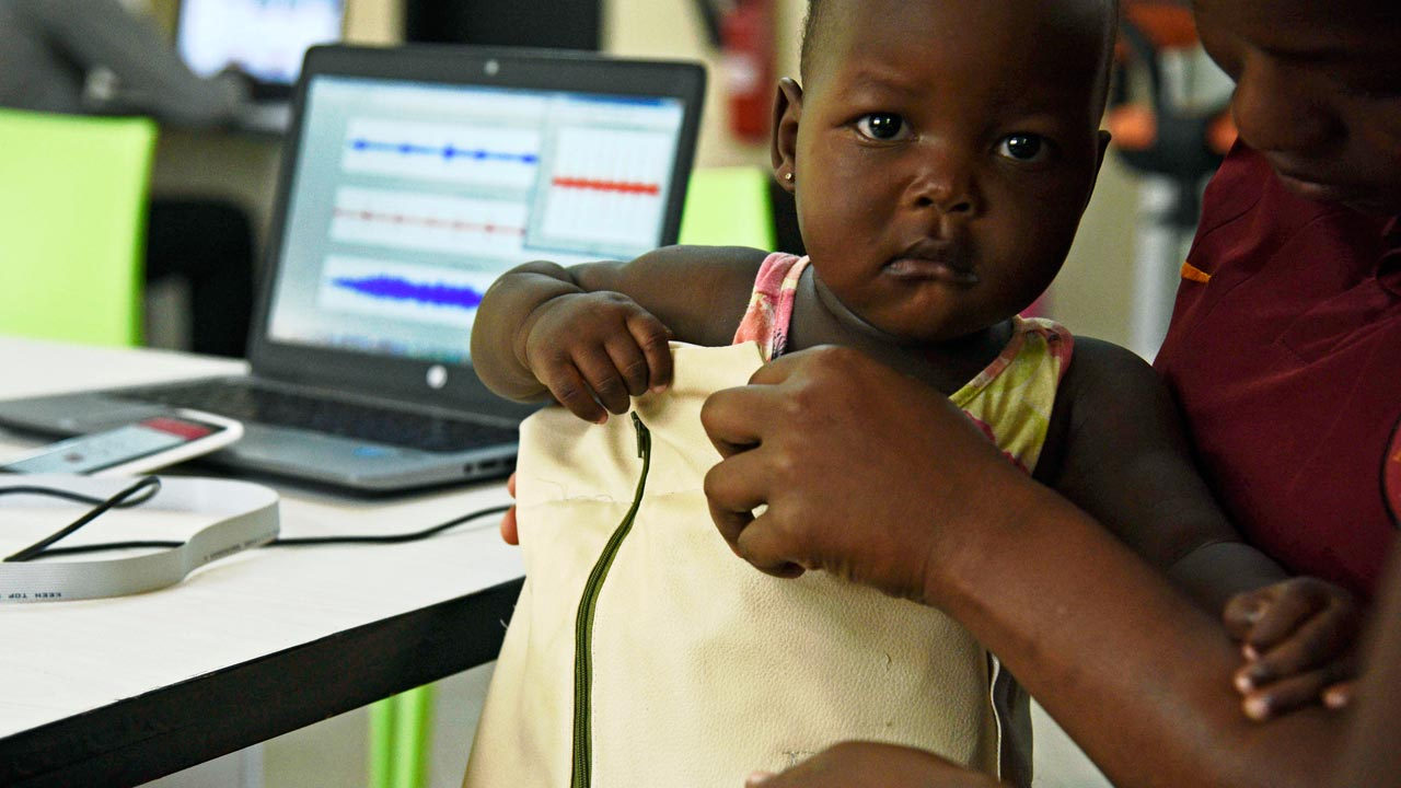 "Telecommunications engineer Olivia Koburongo fits a child with the mama-ope kit at the Makerere University of Public Health in Kampala on January 16, 2017. A team of Ugandan engineers has invented a ""smart jacket"" that diagnoses pneumonia faster than a doctor, offering hope against a disease which kills more children worldwide than any other. ISAAC KASAMANI / AFP"