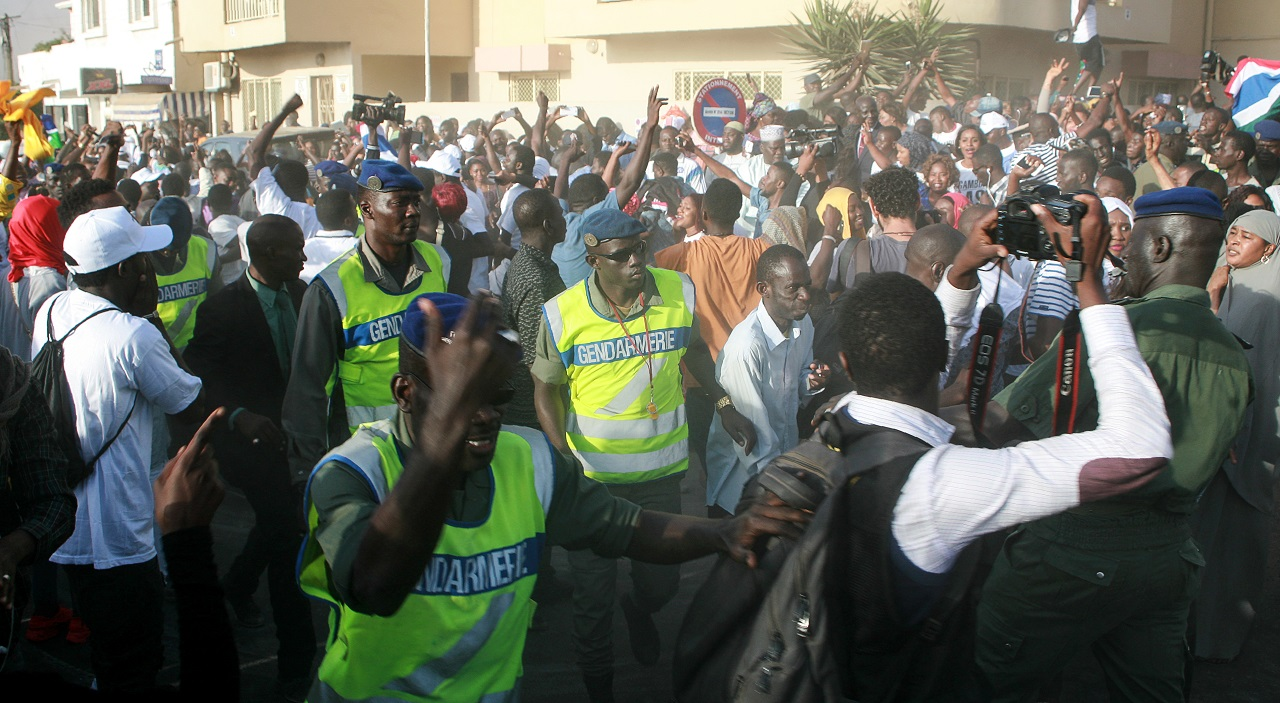 "Gendarmes interfere as supporters celebrate Gambia's President-elect Adama Barrow in front of the Gambian Embassy in Dakar on January 19, 2017. Gambia's new president Adama Barrow took the oath of office in the country's embassy in Senegal on January 18, calling on the country's armed forces to ""demonstrate their loyalty"" in a standoff with Yahya Jammeh, the longtime leader who has refused to step down despite an election defeat. / AFP PHOTO / MOUSSA SOW"