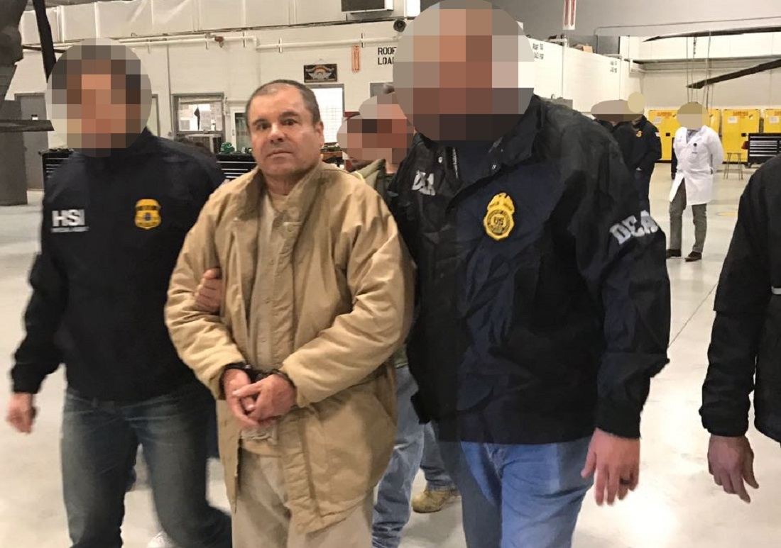 "Handout picture released by the Mexican Interior Ministry on January 20, 2017, shows Joaquin Guzman Loera aka ""El Chapo"" Guzman (C) being escorted by US Drug Enforcement (DEA) personal as he is extradited to the United States on January 19, 2017, in an unknowen location. Mexican drug baron Joaquin ""El Chapo"" Guzman, one of the world's most notorious criminals, was extradited to the United States to face charges on the eve of Donald Trump's inauguration. / AFP PHOTO / Mexican Interior Ministry / MEXICAN INTERIOR MINISTRY / Pixelation of faces was done by Mexican Interior Ministry"