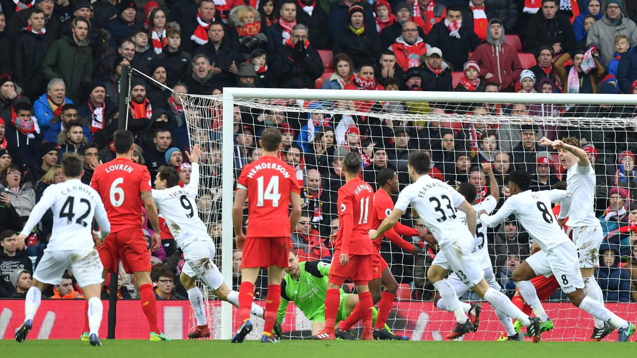 Swansea City's Spanish striker Fernando Llorente (3L) wheels away to celebrate scoring a goal during the English Premier League football match between Liverpool and Swansea City at Anfield in Liverpool, north west England on January 21, 2017. PHOTO: Anthony DEVLIN / AFP