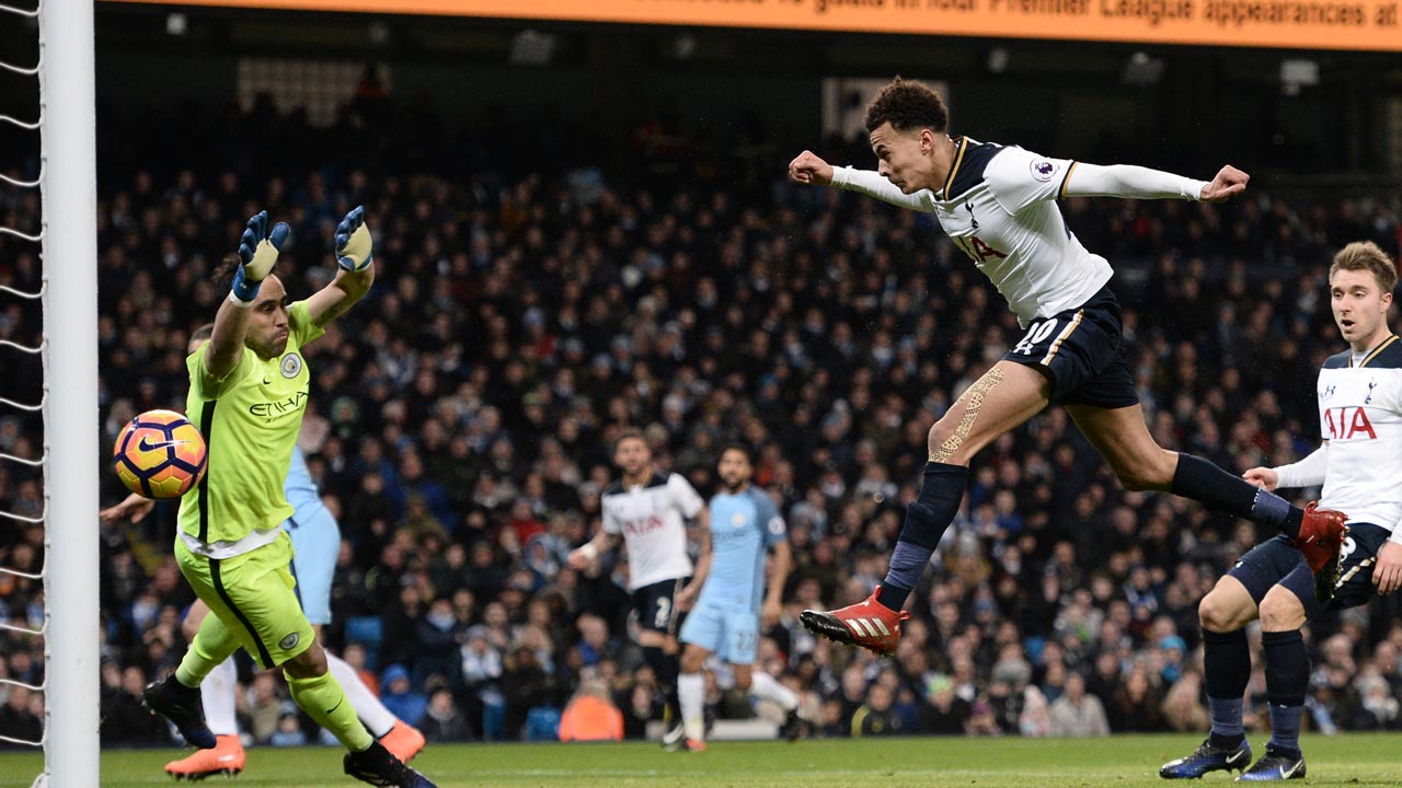 Tottenham Hotspur's English midfielder Dele Alli (2nd R) jumps to head their first goal past Manchester City's Chilean goalkeeper Claudio Bravo (L) during the English Premier League football match between Manchester City and Tottenham Hotspur at the Etihad Stadium in Manchester, north west England, on January 21, 2017.  Oli SCARFF / AFP