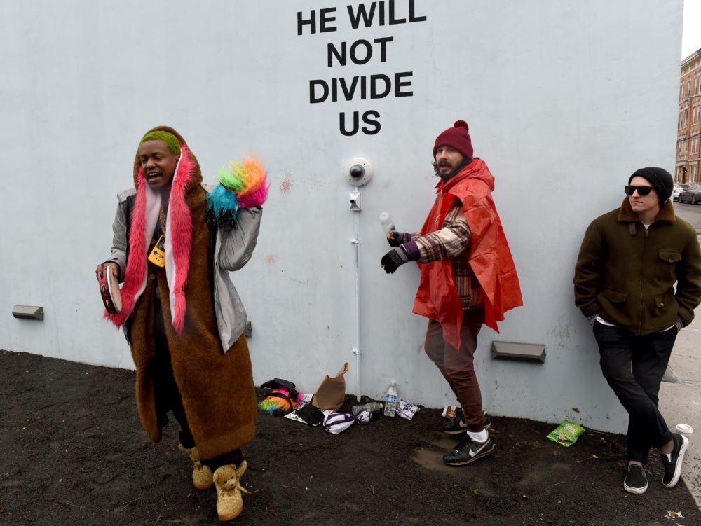 """US actor Shia LaBeouf(C) during his """"He Will Not Divide Us"""" livestream outside the Museum of the Moving Image in Astoria, in the Queens borough of New York January 24, 2017 as a protest against President Donald Trump. LaBeouf has installed a camera at the Museum of the Moving Image in New York that will run a continuous live stream for the duration of Trump's presidency. LaBeouf is inviting the public to participate in the project by saying the phrase, """"He will not divide us,"""" into the camera. / AFP PHOTO / TIMOTHY A. CLARY"""