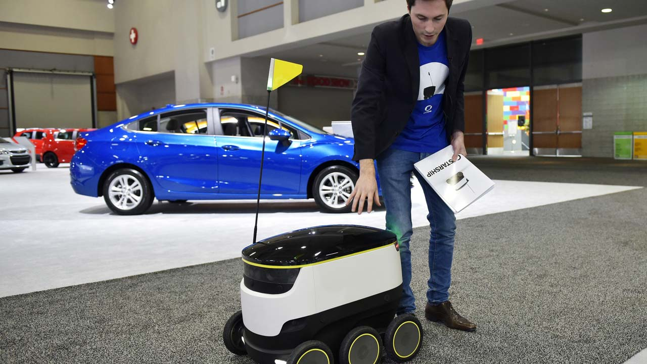 "Henry Harris-Burland explains the operation of the Starship Technologies delivery robot on January 26, 2017 at the Washington Auto Show in Washington, DC. The robots of the future will be coming soon, rolling along at lumbering pace, with those goods you just ordered. The six-wheeled, knee-high robots from startup Starship Technologies are part of a new wave of automated systems taking aim at the ""last mile"" delivery of goods to consumers. MANDEL NGAN / AFP"