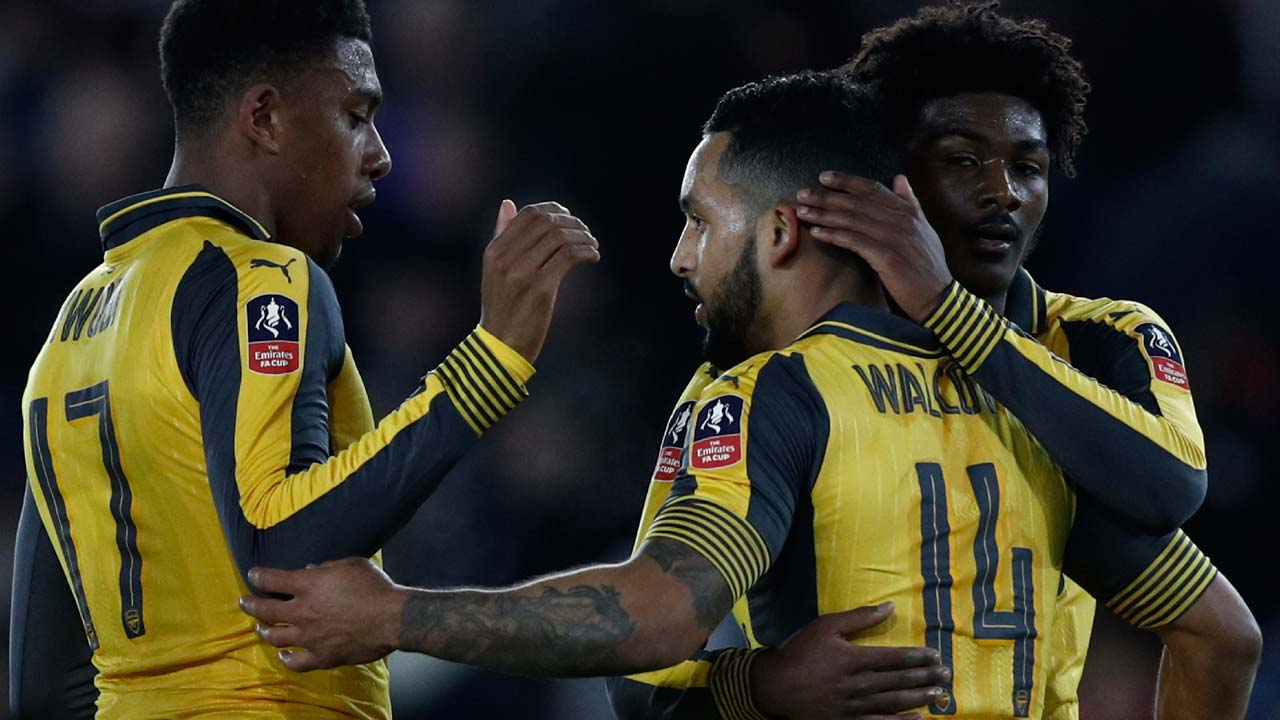 Arsenal's English midfielder Theo Walcott (C) celebrates scoring his team's fifth goal with Arsenal's Nigerian striker Alex Iwobi (L) and Arsenal's English midfielder Ainsley Maitland-Niles during the English FA Cup fourth round football match between Southampton and Arsenal at St Mary's in Southampton, southern England on January 28, 2017. PHOTO: Adrian DENNIS / AFP
