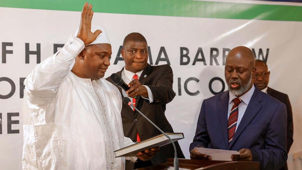 The Gambian President Adama Barrow (left) and the country's Chief Justice, Justice Emmanuel Oluwasegun Fagbenle (right) during the swearing-in of the president in The Gambian Embassy in Senegal …yesterday.