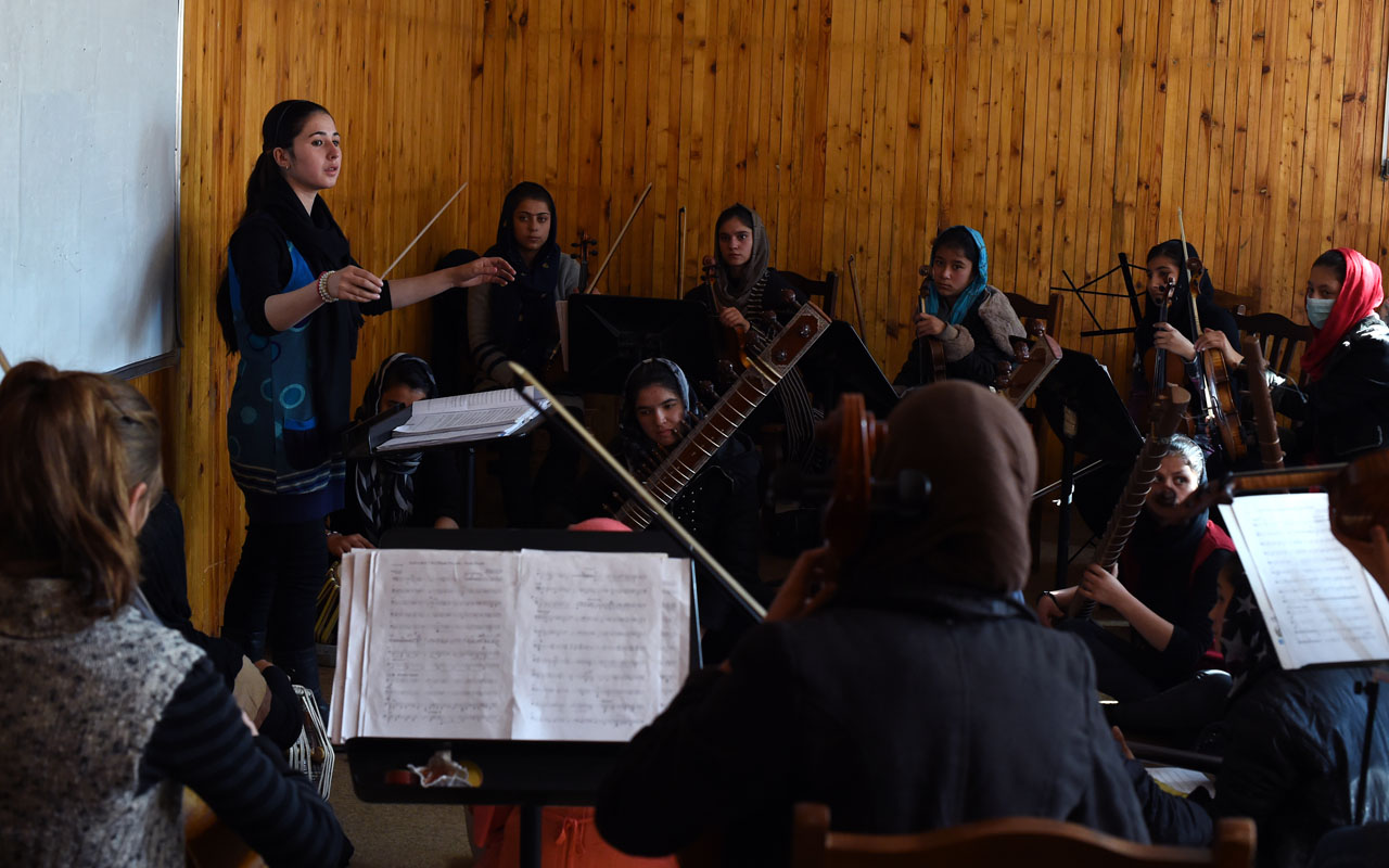 In this photograph taken on January 8, 2017, nineteen year-old Afghan Negina Khpalwak (L), the first female orchestra conductor in Afghanistan, conducts her musicians during a rehearsal at The Afghanistan National Institute of Music in Kabul. In the face of death threats and accusations they are dishonouring their families by daring to perform, the women of Afghanistan's first all-female orchestra are charting a new destiny for themselves through music. The group is set to be catapulted onto the world stage with a performance at the World Economic Forum in Davos. / AFP PHOTO / WAKIL KOHSAR / To go with 'Afghanistan-Music-Gender-Davos-Social' by Anne CHAON