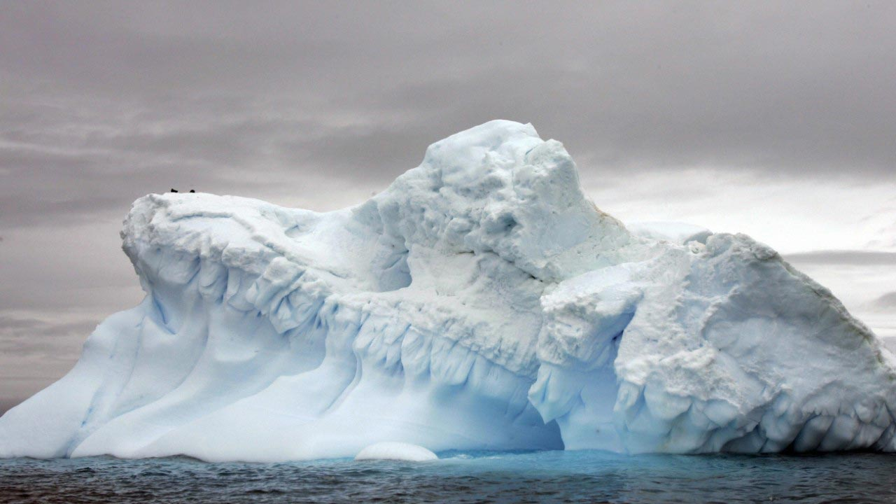 A chunk of ice half the size of Jamaica which is breaking away from West Antarctica is now attached to its parent ice shelf just by a thread, scientists reported Friday.