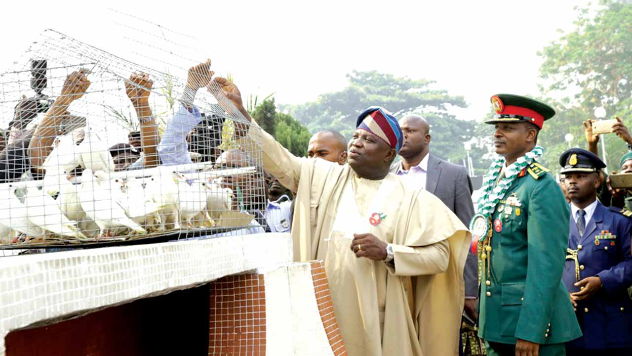 Lagos State Governor Akinwunmi Ambode (left) performing the release of pigeons while the Commander 9 Brigade, Brig. Gen. Sanni Mohammed (right) and others watch with rapt attention at the Remembrance Arcade, Tafawa Balewa Square, Lagos.