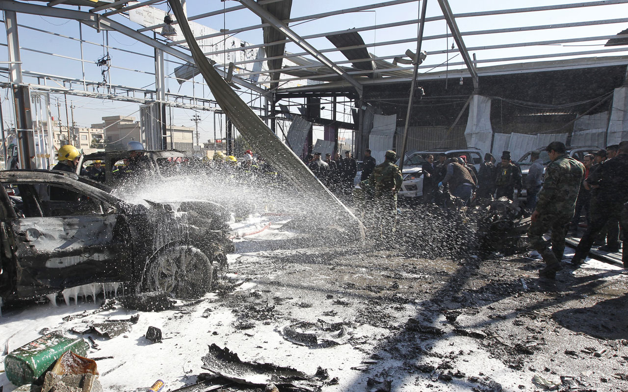 Iraqi firefighters extinguish fire at the site of a car bomb attack at a garage in the capital Baghdad on January 24, 2017. / AFP PHOTO / SABAH ARAR