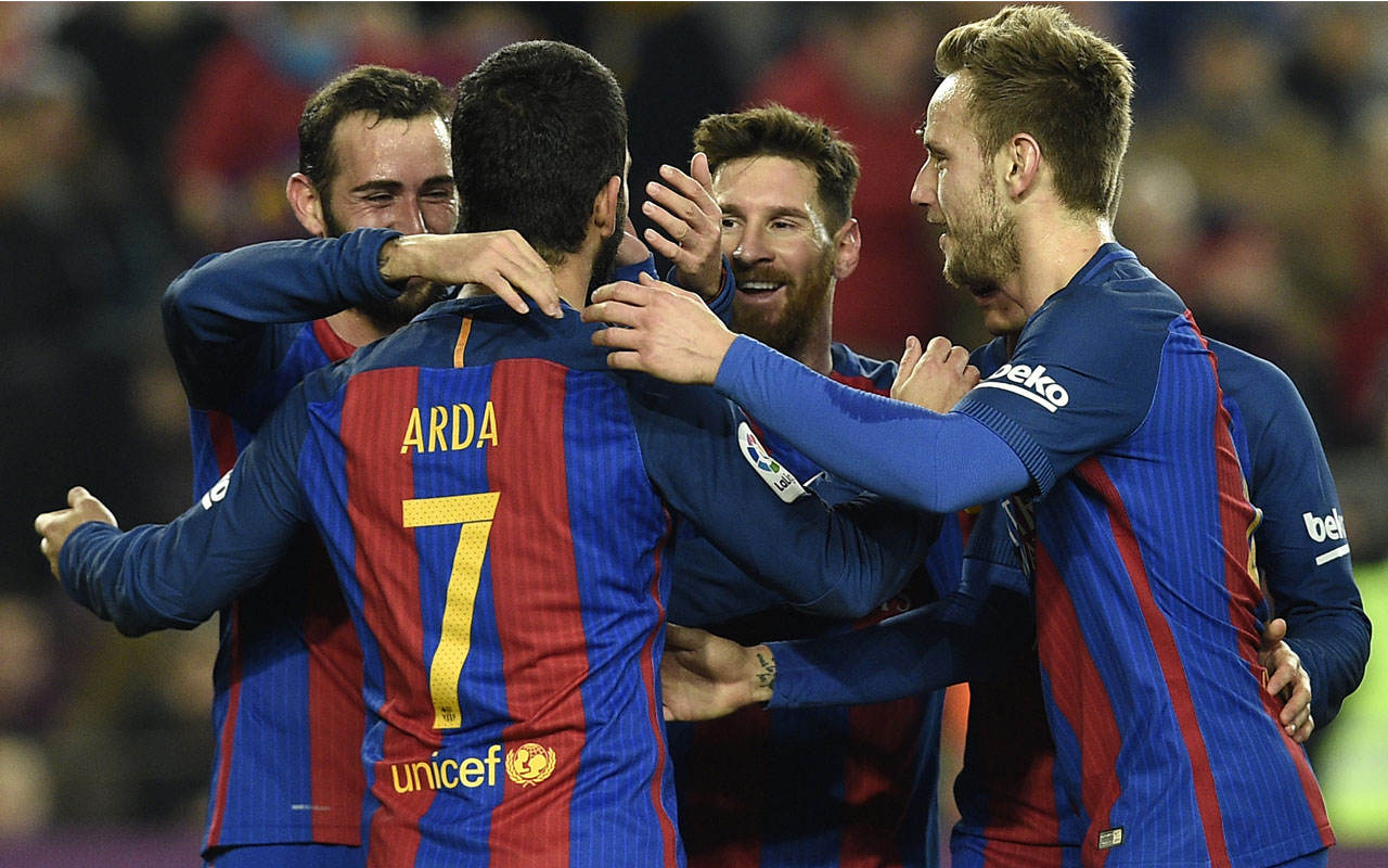 Barcelona's Turkish forward Arda Turan (7) celebrates with teammates after scoring during the Spanish Copa del Rey (King's Cup) quarter final second leg football match FC Barcelona vs Real Sociedad at the Camp Nou stadium in Barcelona on January 26, 2017. / AFP PHOTO / LLUIS GENE