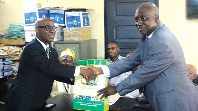 President, Nigerian Council of Registered Insurance Brokers (NCRIB), Emmanuel Kayode Okunoren(left); donating Insurance text books to the Head of Department, Actuarial Science and Insurance, University of Lagos, Professor Ade Ibiwoye , in Lagos