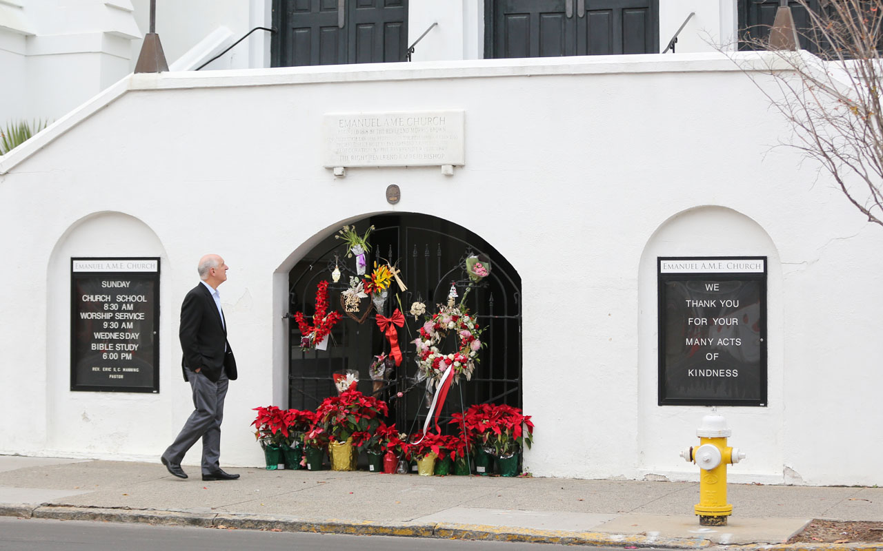 A man stops to observe the makeshift memorial in front of Mother Emanuel AME Church in downtown Charleston, South Carolina on January 4, 2017. Dylann Roof, the self-described white supremacist who gunned down nine black churchgoers in a Charleston church, offered no apology or motive for his actions as a jury began considering whether to sentence him to death. / AFP PHOTO / Logan Cyrus