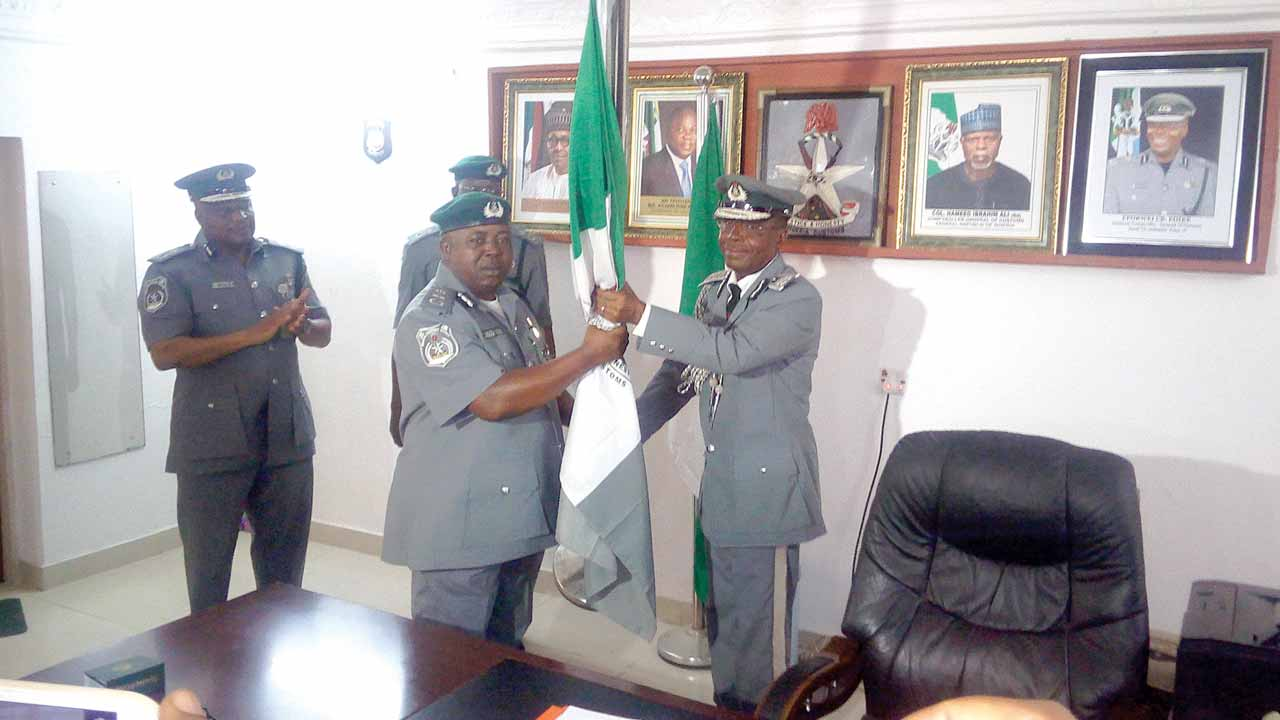 "Former Customs Zonal Coordinator, Zone ""A`, Assistant Comptroller-General Eporwei Edike (right); handling over the staff of office to the new Coordinator, Assistant Comptroller-General Monday Abueh at the Zone 'A' Command of the Nigerian Customs Service in Lagos."