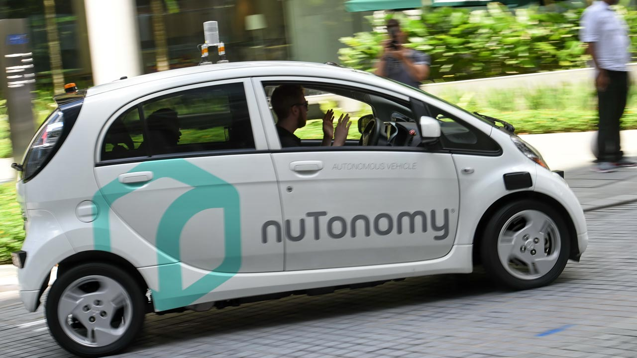 (FILES) This file photo taken on September 23, 2016 shows a safety driver sitting in a moving driverless car during a public trial run in Singapore. Evangelists for driverless cars see a bright future coming down the road: thousands of lives saved, countless driving hours freed up, cityscapes transformed with traffic jams vanquished. ROSLAN RAHMAN / AFP