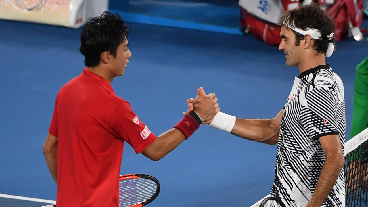 Switzerland's Roger Federer (R) shakes hands with Japan's Kei Nishikori after winning their men's singles fourth round match on day seven of the Australian Open tennis tournament in Melbourne on January 22, 2017. WILLIAM WEST / AFP