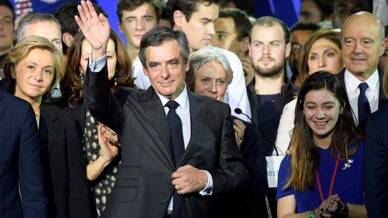 French right wing candidate for the upcoming presidential election Francois Fillon (C), flanked by his wife Penelope Fillon (rear C), by President of the Ile-de-France region Valerie Pecresse (rear L) and by Mayor of Bordeaux Alain Juppe (rear R), salutes the audience at the end of a campaign rally on January 29, 2017 in Paris. The campaign of Fillon, a former prime minister who won the conservative Republicans' nomination last year, has been dealt a serious blow by claims his Welsh-born spouse did nothing to earn half a million euros ($534,000) paid from public funds over eight years. Christophe ARCHAMBAULT / AFP
