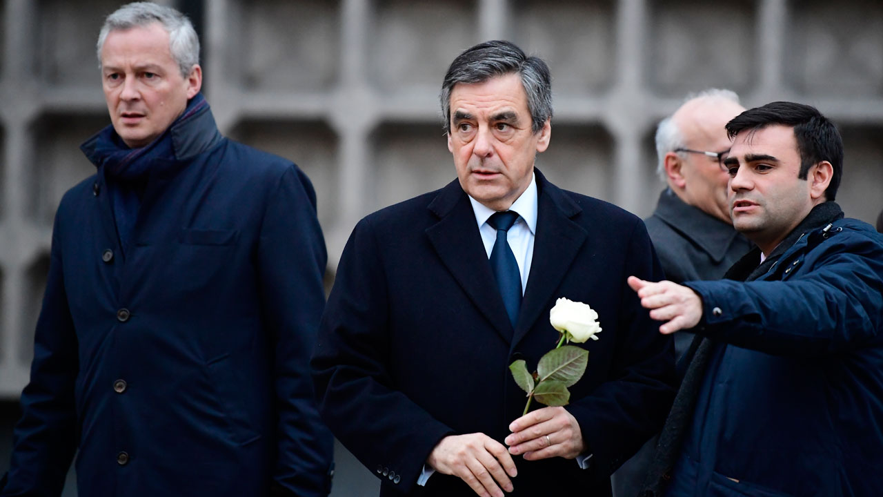 French presidential hopeful Francois Fillon (C), leading candidate of the Republicans party, arrives to lay down a flower at the site of the Christmas market attack on January 23, 2017 in Berlin. On December 19, 2016, suspected jihadist attacker Anis Amri ploughed a hijacked truck into a Berlin Christmas market, killing 12 people, including the vehicle's registered driver. Tobias SCHWARZ / AFP